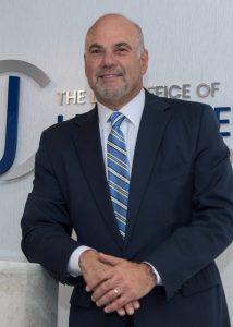 Jay Cohen standing at reception desk, smiling