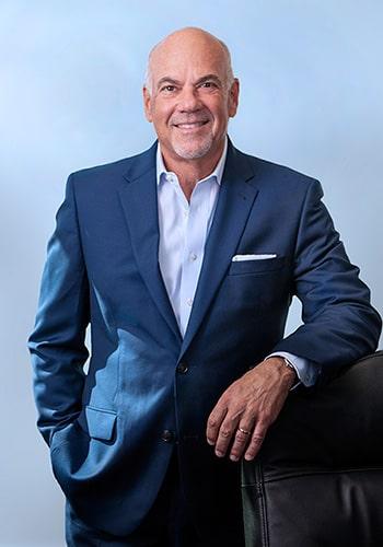 Jay Cohen portrait leaning on desk chair, blue background