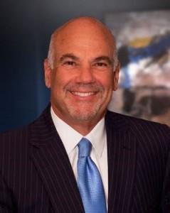 Jay Cohen smiling, image taken in dark blue conference room