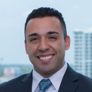 Rudy Ayala headshot, standing in front of window