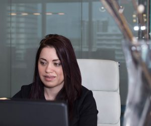 photo of Receptionist sitting at her desk, smiling