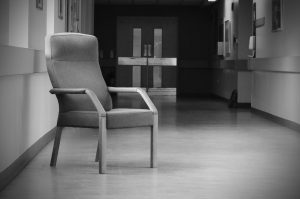 monochrome image of chair in hospital hallway